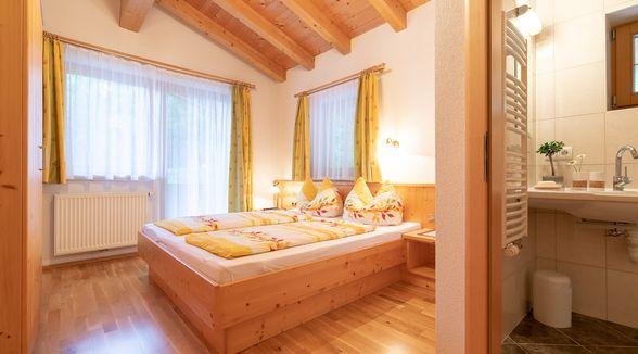 Schlafzimmer mit Fensterfront, Doppelbett und Blick ins Bad